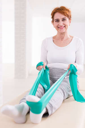 Foto per Happy elderly pretty woman in physiotherapist's office sitting on a treatment table. Strengthening her legs with elastic band - Immagine Royalty Free