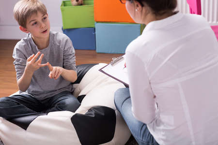 Foto de Shot of a little boy talking to a psychologist - Imagen libre de derechos