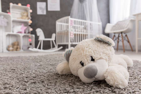 Photo pour Shot of a teddy bear laying on a carpet in a cozy baby girl room - image libre de droit