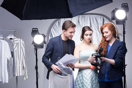 Photo for Young red-haired photographer in a photo studio showing photos on the camera display to a model and an assistant - Royalty Free Image