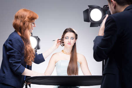 Photo for Young model having her strong makeup finished during shooting a portrait photo in a studio - Royalty Free Image