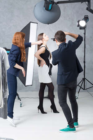 Photo for Fashion session in a photographic studio, with a model in a black and white dress, a photographer and his assistant - Royalty Free Image