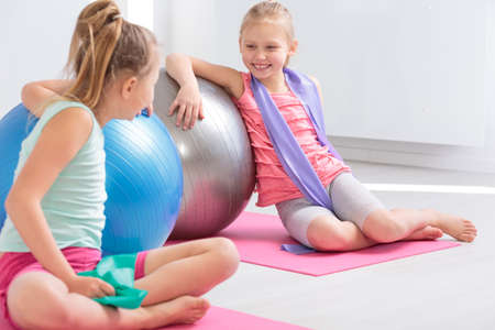 Photo pour Two little friends resting against large exercise balls after finished exercises, smiling and chatting - image libre de droit