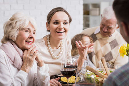 Photo pour Multi-generational family talking and enjoying dinner together - image libre de droit