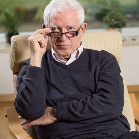 Foto de Portrait of senior psychotherapist sitting on armchair - Imagen libre de derechos