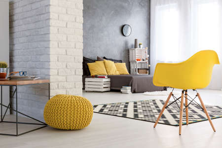 Photo pour Spacious bedroom with white brick wall. Wooden coffee table and yellows chairs. By the wall grey bed with yellow pillows - image libre de droit