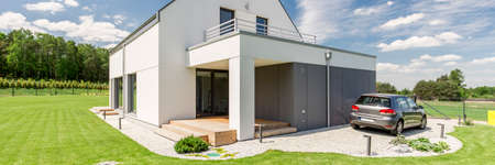Photo pour Panoramic photo of a modern house in the country with a car on the driveway in front of it - image libre de droit