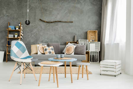 Photo for Image of a new style grey flat with DIY furniture, sofa, small table and chairs - Royalty Free Image