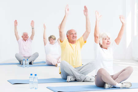 Photo for Group of active seniors during yoga workout, light interior - Royalty Free Image