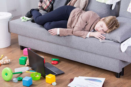 Photo pour Young mother sleeping in her office clothes on a sofa in a messy living room - image libre de droit