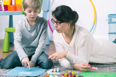 Photo pour Boy and female pedagogue working with commitment on the carpet - image libre de droit
