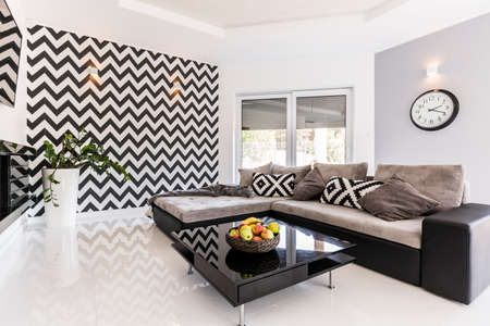 Photo pour New style spacious living room with large sofa, black small table and pattern wallpaper - image libre de droit
