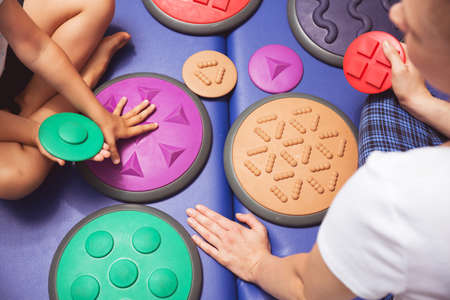 Photo pour Girl's and therapist's hands touching the various shaped mat - image libre de droit