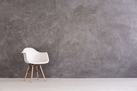 Foto de White plastic chair on a background of a gray concrete wall - Imagen libre de derechos