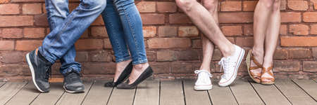 Photo pour Close-up of young people legs on red brick wall - image libre de droit