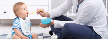 Foto de Small baby eating from a spoon, father feeding his child, panorama - Imagen libre de derechos