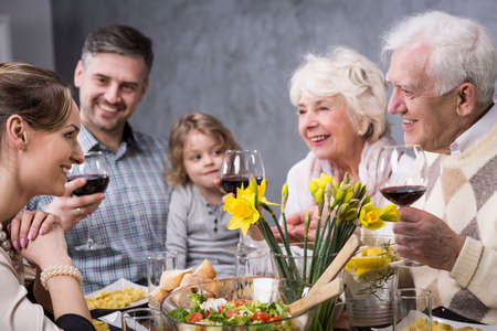 Photo pour Three generations of the family are involved in a discussion during  family dinner - image libre de droit