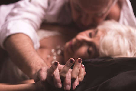 Photo for Elder couple lying together on a bed in an erotic love hug with intertwined fingers - Royalty Free Image