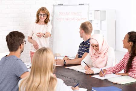 Photo pour Multicultural language class and positive mature teacher - image libre de droit