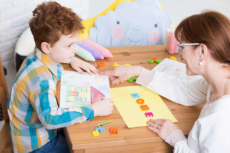 Photo pour Therapy session with the therapist teaching the young boy alphabet - image libre de droit