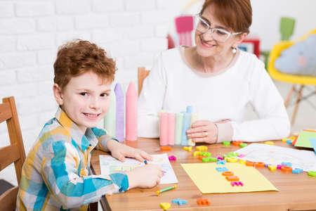Foto de Therapy center interior with the smiled boy and his psychologist - Imagen libre de derechos
