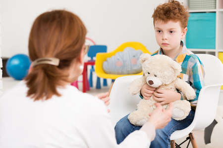 Photo pour Red-haired, autistic boy with teddy bear concentrated on his therapist - image libre de droit