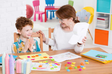 Foto de Red-haired boy satisfied with the alphabet learning with the speech therapist - Imagen libre de derechos