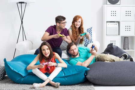 Photo pour Group of young friends sitting on modern poufs, playing video games - image libre de droit
