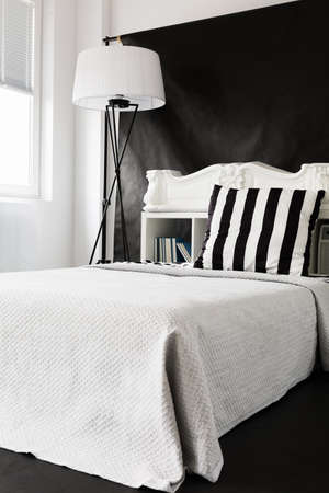 Black and white ascetic style bedroom with large bed and floor lamp