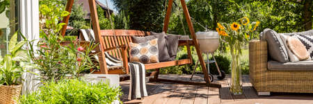 Photo for Cozy house terrace with wooden garden swing and a grill - Royalty Free Image