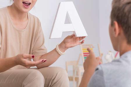 Photo pour Shot of a little boy having a meeting with speech therapist - image libre de droit