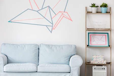 Foto de Light living room with sofa, DIY regale and washi tape wall decor - Imagen libre de derechos