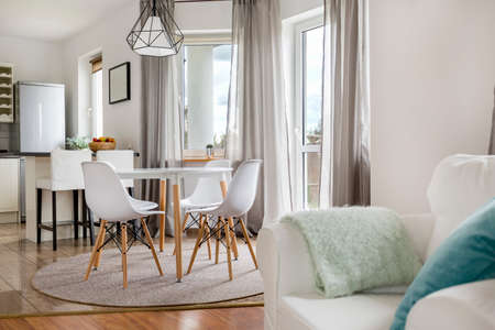 New flat with round table, white chairs and open kitchen