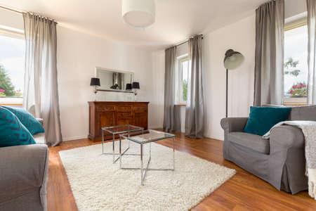 Foto de Cozy living room with decorative window curtains, glass coffee table, sofa and armchair - Imagen libre de derechos
