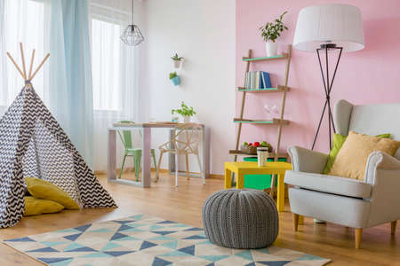 Foto de Spacious interior in pink and white with play tent, armchair, pouf, two chairs and table - Imagen libre de derechos