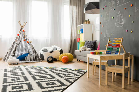Photo for Spacious child room with window, play tent, sack chair, pattern carpet, regale, sofa, small table, chairs and blackboard wall - Royalty Free Image