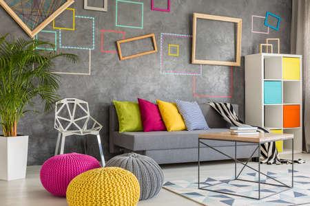 Foto de Colorful living room with decorative grey wall and wool poufs - Imagen libre de derechos