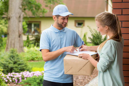 Photo pour Young courier holding a parcel, woman signing a delivery form - image libre de droit
