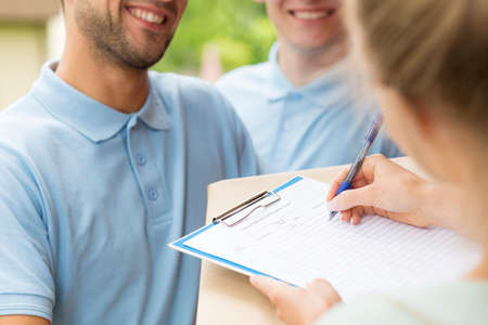 Photo pour Close up of a two couriers with a parcel and woman signing a delivery form - image libre de droit