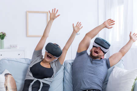 Photo pour Young man and woman wearing VR glasses having fun with a virtual roller coaster - image libre de droit