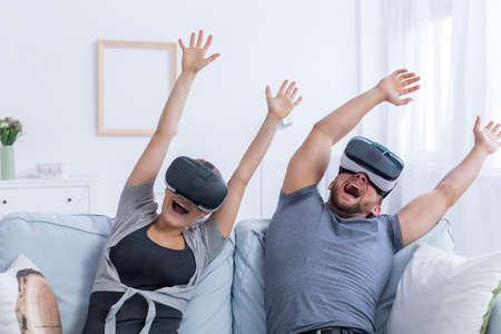 Foto de Young man and woman wearing VR glasses having fun with a virtual roller coaster - Imagen libre de derechos