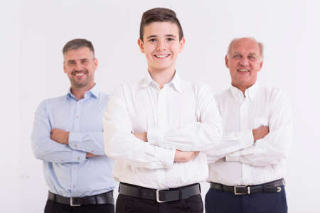 Photo pour Three generations of men standing with folded arms and smiling - image libre de droit