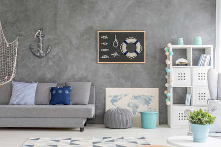 Photo for Grey home interior with nautical wall decor, sofa, carpet and white storage unit - Royalty Free Image