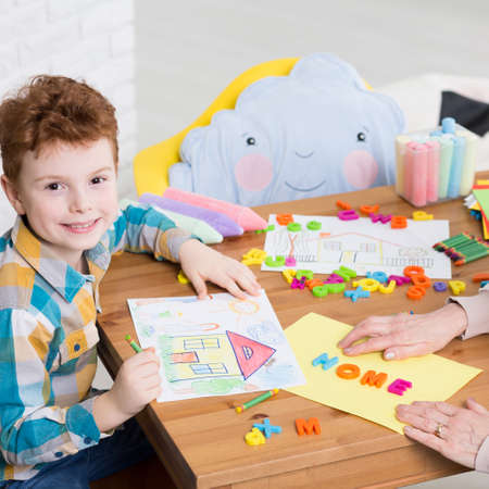 Photo pour Boy drawing a home during occupational therapy - image libre de droit
