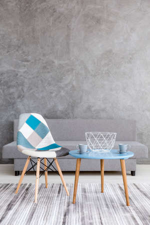 Foto de Acsetic style living room with grey cement wall effect, sofa, patchwork chair, two cups standing on a small table - Imagen libre de derechos