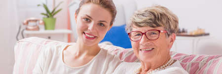 Photo for Happy daughter and her senior mother sitting together on a sofa, panorama - Royalty Free Image