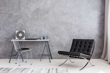 Foto de Ascetic home interior with grey wall, modern chair, lounge chair, cd music collection lying on a simple desk - Imagen libre de derechos