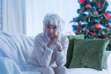 Foto de Senior woman sitting alone on sofa, christmas tree in background - Imagen libre de derechos