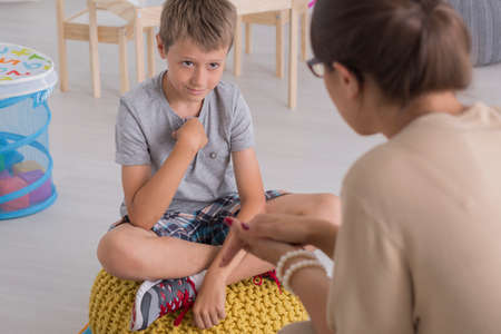 Photo for Sad young boy sitting on a pouf, talking with a psychologist - Royalty Free Image