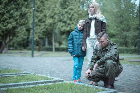 Photo pour Photo of a soldier and his family visiting grave - image libre de droit